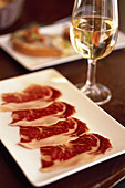Spain. Andalusia. Jerez. Local cooking tapas. Slices of Jabugo ham pata negra and Sherry at the restaurant Gallo Azul