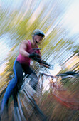 ability, activity, adult, bicycle, bicyclist, biker, blurred motion, Color image, contemporary, cycle, cycling, day, effort, exercise, eye, Female, fit, full length, health, healthy, human, leisure, motion, mountain biking, moving, one, one person, outdoo