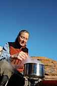 Woman cooking meal. Zion NP. Utah . USA