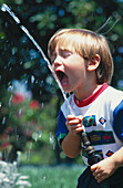 Boy drinking from hose