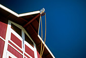 Barn, Barns, Blue, Building, Buildings, Color, Colour, Concept, Concepts, Daytime, Detail, Details, Exterior, Farm, Height, Horizontal, Low angle view, Outdoor, Outdoors, Outside, Pulley, Pulleys, Red, Rope, Ropes, Summer, Tall, Tool, Tools, Useful, Usef