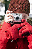 young girl in winter taking photos