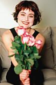20-30 Jahre, 25-30 Jahre, 30-35 Jahre, 30-40 Jahre, Blick Kamera, Blume, Blumen, Blumenstrauss, Dunkelhaarig, Eine Person, Eins, Erwachsene, Erwachsener, Farbe, Frau, Frauen, Frauen (nur), Freude, Geschenk, Geschenke, Gesichtsausdruck, Gesichtsausdrücke,