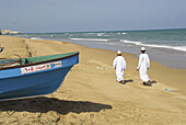 Local Omani youths walking along the beach at Sifa, a popular recreational and fishing village near Muscat, Oman