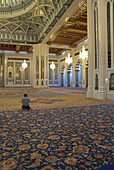 Lone muslim praying, kneeling on the world s largest single carpet, in the main hall of the Sultan Qaboos Grand Mosque, Muscat, Oman