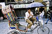 Young man playing a flute on rickshaw. Kathmandu. Nepal