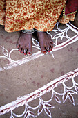 Indian woman on mandana (colourful floor design), village near Tonk. Rajasthan. India