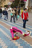 China. Yunnan province. City of Lijiang. UNESCO World Heritage. Contorsionist beggar.