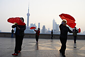 China. Shanghai. Chinese women dance with red fans on the bund in Shanghai for exercise every morning.