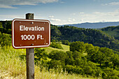 Elevation marker sign and rolling green hills and oak trees in spring, Mount Diablo State Park, California
