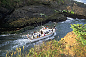 Fishing boat heading to sea between narrow rock channel, world s smallest natural navigable harbor, Depoe Bay, Oregon Coast