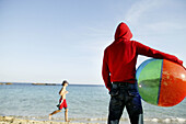 Adult, Adults, Back view, Ball, Balls, Beach, Beach ball, Beach balls, Beaches, Coast, Coastal, Color, Colour, Contemporary, Contrast, Contrasts, Daytime, Exterior, Fit, Hold, Holding, Hood, Hoods, Human, Knees-up, Leisure, Outdoor, Outdoors, Outside, Pa