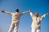 Couple raising arms