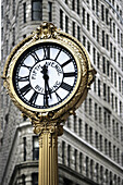 Clock with Flatiron Building in background. New York City. USA