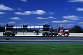Blurred, Color, Colour, Daytime, Economy, Exterior, Fast, Freight transportation, Highway, Highways, Industrial, Industry, Lorries, Lorry, Motion, Movement, Moving, Outdoor, Outdoors, Outside, Road, Road tanker, Road tankers, Roads, Shipping, Speed, Thor