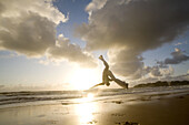 Capoeira player training and exercising in the beach, Brazil.