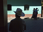 A man waits in the shade to escape the mid day heat on streets of San Lucas Toliman, Guatemala, near Lake Atitlan