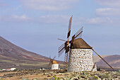Old windmill and volcanoes in background, La Olivia. Fuerteventura. Canary Islands. Spain