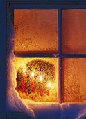 Candles in a frosty window