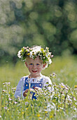 Two year old girl with wreath made of flowers in direct light. Västerbotten, Sweden