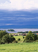 Houses and thunder clouds over lake Orsa. Naset, Dalarna, Sweden