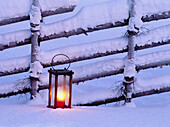 Lantern with candle in front of snow-covered fence. Skelleftea, Västerbotten, Sweden
