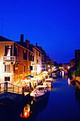 Restaurant on canal at dusk. Venice. Italy