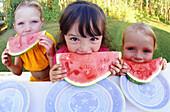 Three girls eating watermelon outdoors