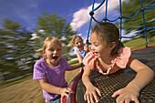 Children playing on merry go round at playground