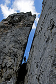 Silhouette of person in a crevice, mount Kopftoerl, Kaiser range, Tyrol, Austria