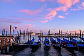 Couple and boats (gondolas) in twilight, San Marco, Venice, Venezia, Italy
