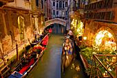 Boat (gondolas) in front of illuminated restasurant at dusk, Venice, Venezia, Italy
