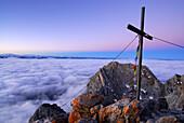 Summit cross with prayer flags on mountain Ellmauer Halt, Kaiser range, Tyrol, Austria