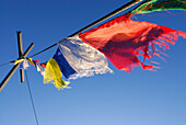 Prayer flags at summit cross on mountain Ellmauer Halt, Kaiser range, Tyrol, Austria