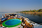 cruise on the Nile, view from upper deck to pool on deck and palm trees at western bank, Nile between Luxor and Dendera, Egypt, Africa