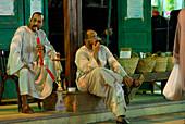 two men, one smoking water pipe (hookah), street scene at night, market in Aswan, Egypt, Africa