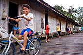 Children playing in front of Long house of the Iban People, Kuching, Sarawak, Borneo, Malaysia