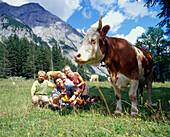 Family sitting in grass near a cow, Eng, Kleiner Ahornboden, Tyrol, Austria