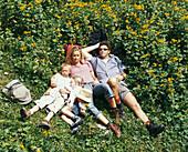 Family lying on grass, Eng, Kleiner Ahornboden, Tyrol, Austria