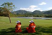 Two women sitting on the grass, caddy, Kirimaya Golf Course, Khao Yai National Park, Thailand