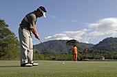 Man playing golf, Golf player and caddy, Kirimaya Golf Course, Khao Yai National Parc, Thailand