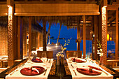 A set table inside Reethi Restaurant at night, One & Only Resort Reethi Rah, Maldives