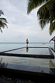 Woman walking near the pool, One & Only Resort Reethi Rah, Maldives, no MR