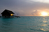 Sunset over sea with water villa, One & Only Resort Reethi Rah, Maldives