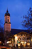 Christmassy decorated and illuminated house in the evening, church St. Martin in background, Garmisch, Garmisch-Partenkirchen, Germany