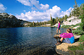 Kids enjoying the view along the shore of Boothe Lake, in the Cathedral Range, Sierra Nevada Mountains. Yosemite NP. California. USA