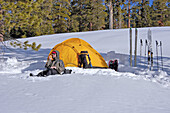 Skier using a radio and yellow dome tent in a backcountry ski camp, Yosemite National Park, California