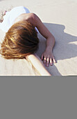 Abandoned, Abandonment, Adult, Adults, Arm, Arms, Beach, Beaches, Caucasian, Color, Colour, Contemporary, Daytime, Exterior, Female, Human, Languid, Languor, Lying down, One, One person, Outdoor, Outdoors, Outside, People, Person, Persons, Posture, Postu