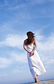 Adult, Adults, Alone, Back view, Blue, Blue sky, Calm, Calmness, Color, Colour, Contemporary, Daytime, Dress, Dresses, Exterior, Female, Freedom, Full-body, Full-length, Human, Long hair, Long haired, Long-haired, One, One person, Outdoor, Outdoors, Outs