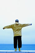 Adult, Adults, Alone, Baby boomer, Baby boomers, Back view, Blue, Color, Colour, Contemporary, Daytime, Exterior, Female, Full-body, Full-length, Future, Horizon, Horizons, Human, Leisure, Middle- age, Middle-aged, One, One person, Open arms, Outdoor, Ou